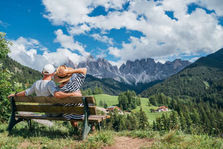 Hugging couple dressed striped white tops sitting on bench enjoying Santa Maddalena village view and stunning picturesque Dolomite Alps in Val di Funes valley, South Tyrol, Italy. Love dating concept.