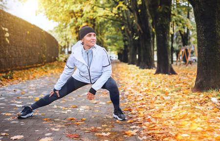 Fit athletic woman doing workout before jogging in autumnal city park on the kids playground. Young fitness female runner stretching legs while warming up. Active runners people concept image.