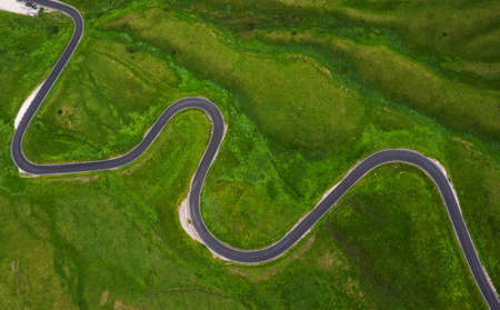 Passo di Giau Green hills Aerial drone shot of curved mountainous snake road. Traveling, transportation, safety driving, traveling, car rental concept. 免版税图像