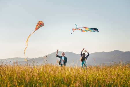 Summer outdoor photo of smiling father with daughter as they releasing colorful kites on the high grass meadow. Warm family moments or outdoor time spending concept image. 免版税图像