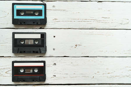 3 Compact Cassettes famous Magnetic audio tape manufacturers lying on white wooden table. Retro and vintage audio music reproduction concept image. 免版税图像