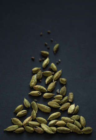 Vertical small DOF close up photo of Cardamom pods and seeds pile on the matt black background. It is very popular in Indian and Sri Lanka cuisine.