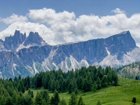 Picturesque Dolomite Alps formation Landscape photo with green spruces hill near Cinque Torri in South Tyrol, Italy. Beauty in Nature and mountain concept image.