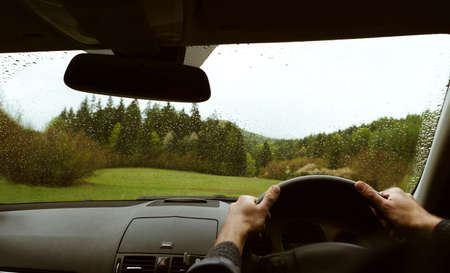 Driver driving a modern off road right hand drive RHD car on the mountain green forest country road at rainy moody day. POV inside car windshield view point. Safely auto driving concept. 免版税图像