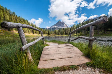 Wooden bridge wide angle photo on Italian  Lago d'Antorno or Antorno Lake with stunning Tre Cime di Lavaredo 2999m peaks on the background in Belluno province, northern Italy.