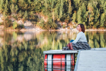 Middle-aged woman on the wooden pier on the mountain enjoying calm lake water during her walking in the autumn season time. Outdoor time spending in nature concept image.