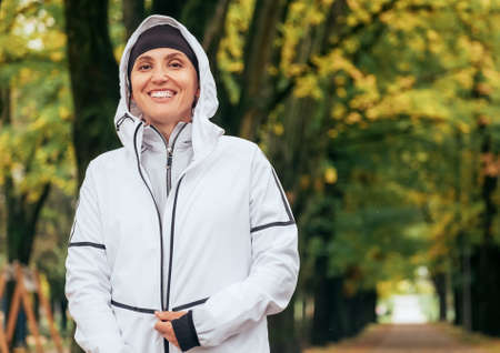 Sincerely smiling Fit athletic woman wearing a modern waterproof running jacket with colorful green yellow autumn park background. Active people concept image.