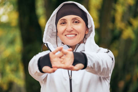A smiling Fit athletic woman wearing a modern waterproof running jacket stretching wrists and fingers in colorful green yellow autumn park. Active sporty people concept image.