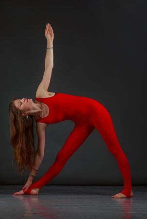 jumpsuit: Beautiful woman in a red jumpsuit doing yoga Stock Photo