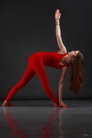 Beautiful woman in a red jumpsuit doing yoga Stock Photo