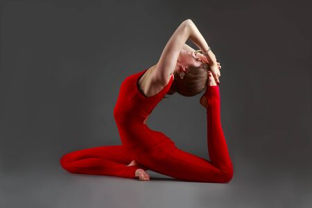 ushtrasana: Beautiful woman in a red jumpsuit doing yoga Stock Photo