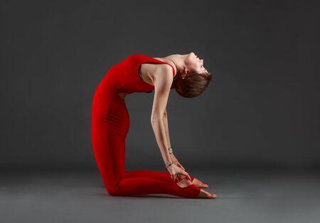 dhanurasana: Beautiful girl in red jumpsuit does yoga