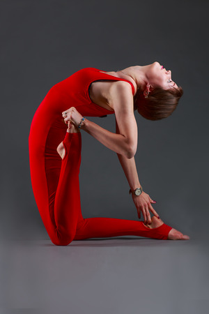 jumpsuit: Beautiful girl in red jumpsuit does yoga