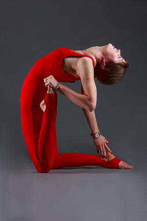 ushtrasana: Beautiful girl in red jumpsuit does yoga