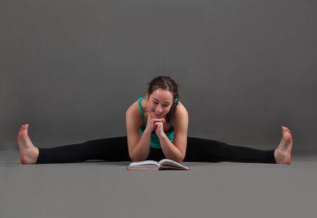 konasana: beautiful woman doing yoga   upavishta konasana on a gray background
