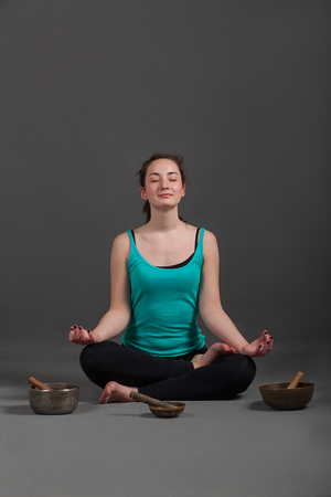 singing bowls: Womaan playing  singing bowls and tools for meditation.
