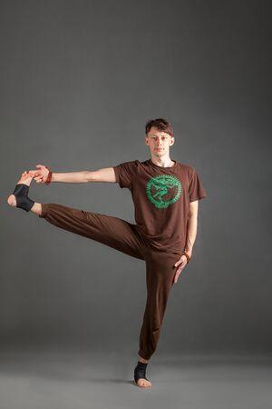 hasta: beautiful man doing yoga on a white background