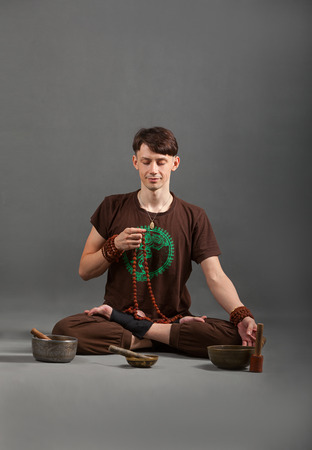 singing bowls: Man playing the flute, singing bowls and tools for meditation. Stock Photo