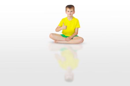 baddha: little boy doing yoga on white background