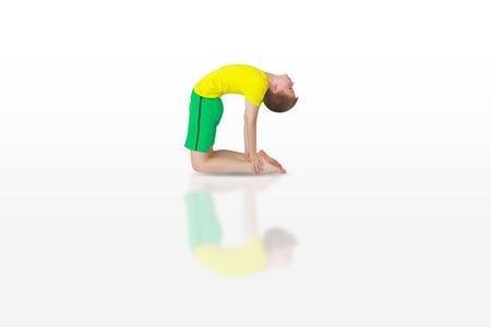 ushtrasana: little boy doing yoga on white background