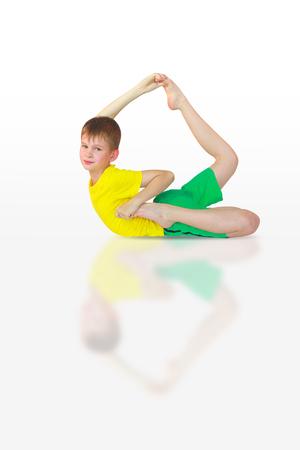 dhanurasana: little boy doing yoga on white background