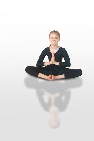 little girl doing yoga on white background