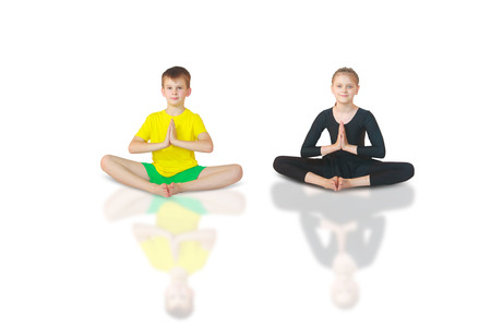 little boy and girl doing yoga on white background Stock Photo