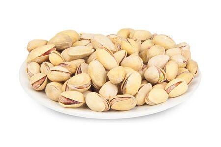 délicieux pistaches sur une plaque sur un fond blanc