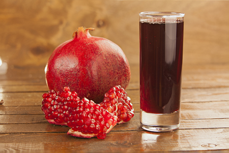 delicious juice from ripe pomegranate in beautiful glass on a wooden table