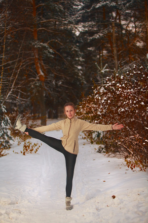 hasta: beautiful woman doing yoga outdoors in the snow
