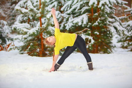beautiful woman doing yoga outdoors in the snow in yellow T-shirt Stock Photo