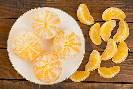 ripe juicy Spanish mandarins on plate on a wooden background