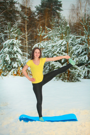hasta: beautiful woman doing yoga outdoors in the snow in yellow T-shirt Stock Photo