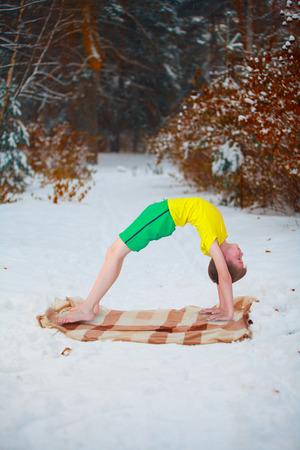 dhanurasana: handsome boy doing yoga outdoors in winter