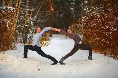 two beautiful women doing yoga outdoors in the snow