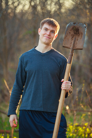 flower beds: Agronomist handsome strong man with shovel on the background of flower beds