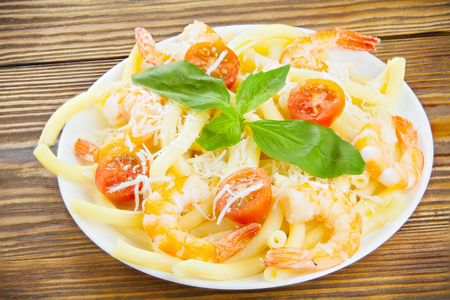 delicious delicious spaghetti with shrimps and basil on a plate on a wooden background