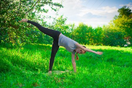 ardha: beautiful woman doing yoga outdoors On the green grass