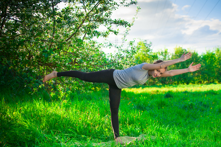 beautiful woman doing yoga outdoors On the green grass