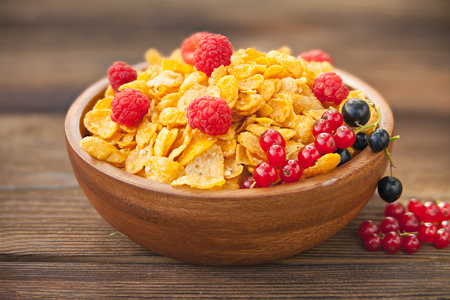 Breakfast of cornflakes with berries in a wooden bowl Stok Fotoğraf