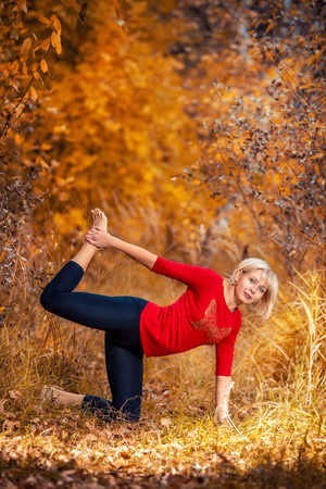 beautiful woman doing yoga outdoors On the yellow leaves Stock Photo