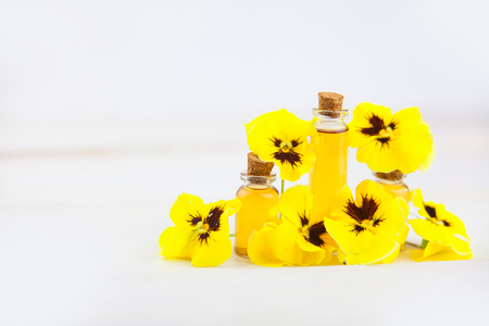 pansies essential oil in a beautiful bottle on the  White background