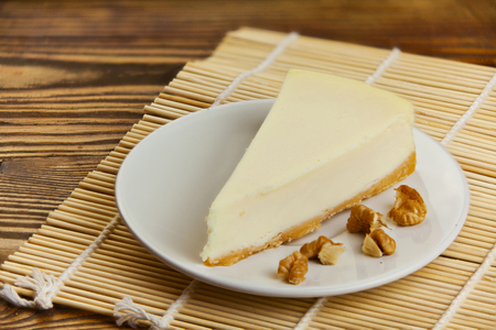 classic cheesecake on a white plate on a woodentable