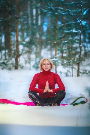 beautiful woman doing yoga outdoors in the snow in yellow T-shirt Фото со стока