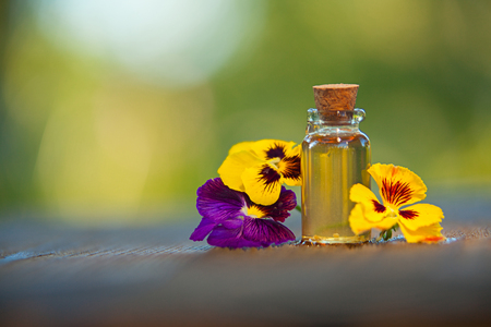 pansies essential oil in a beautiful bottle on the  wooden background