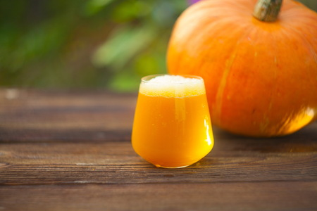 glass of pumpkin juice on a wooden background