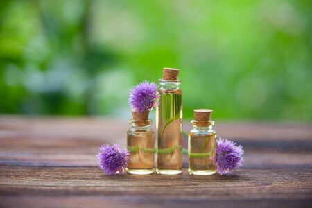 Chives essential oil in a beautiful bottle on the wooden background