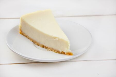 classic cheesecake on a white plate on a white table