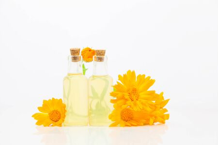 Essence of flowers on White background in a beautiful glass bottle