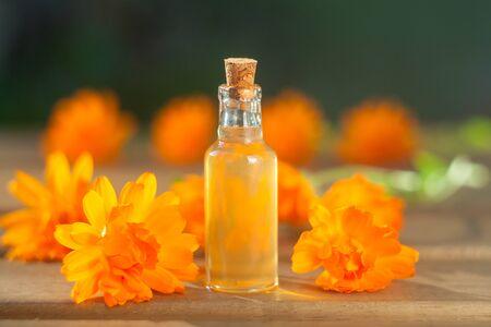 Essence of flowers on table in beautiful glass bottle
